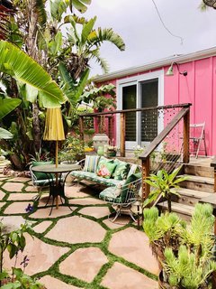The lush tropical backyard features multiple cozy entertaining spaces.