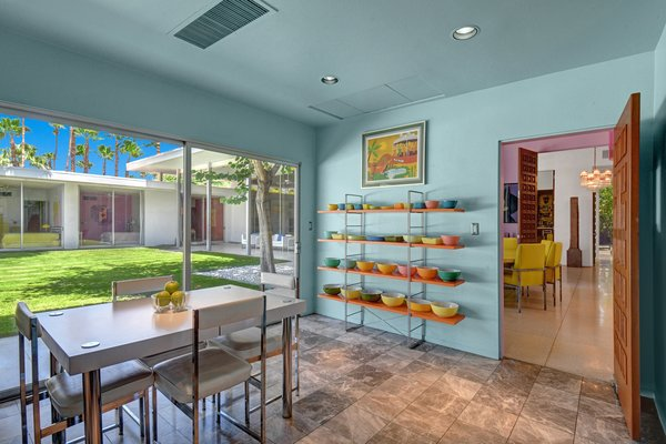 The eat-in kitchen is painted turquoise, and the formal dining room is painted purple to match the bloom colors of the twin orchid trees on either side. In the kitchen, the current homeowners display their colorful collection of vintage pyrex bowls, which remind them of their childhood. The kitchen features marble tile flooring which was added at some point over the years.