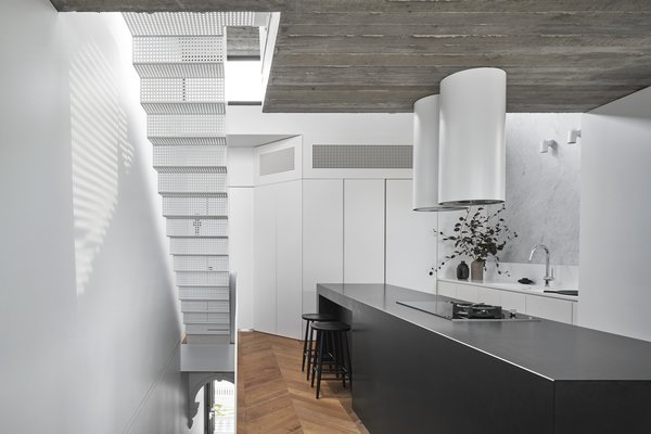 The floating, perforated staircase allows light from a skylight to filter down to the ground floor.