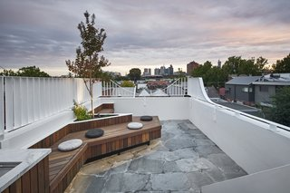 The roof deck features a full outdoor kitchen, custom seating that wraps a tree, and spectacular city views.