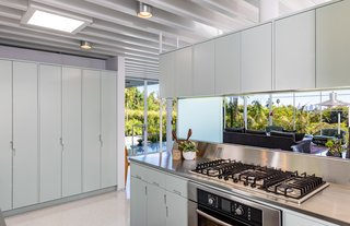 The period-appropriate kitchen is painted in Corbusier's Ceruleum Pale and features cabinets designed with integrated handles.