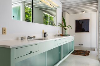 The terrazzo-floored master bath features cabinetry painted in Corbusier's Ceruleum Pale. The millwork incorporates sliding Factro-Lite glass panels.