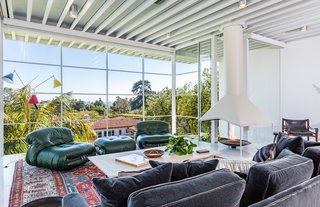The expansive living space features floor-to-ceiling walls of glass. The tall steel-framed ceiling adds to the midcentury charm.