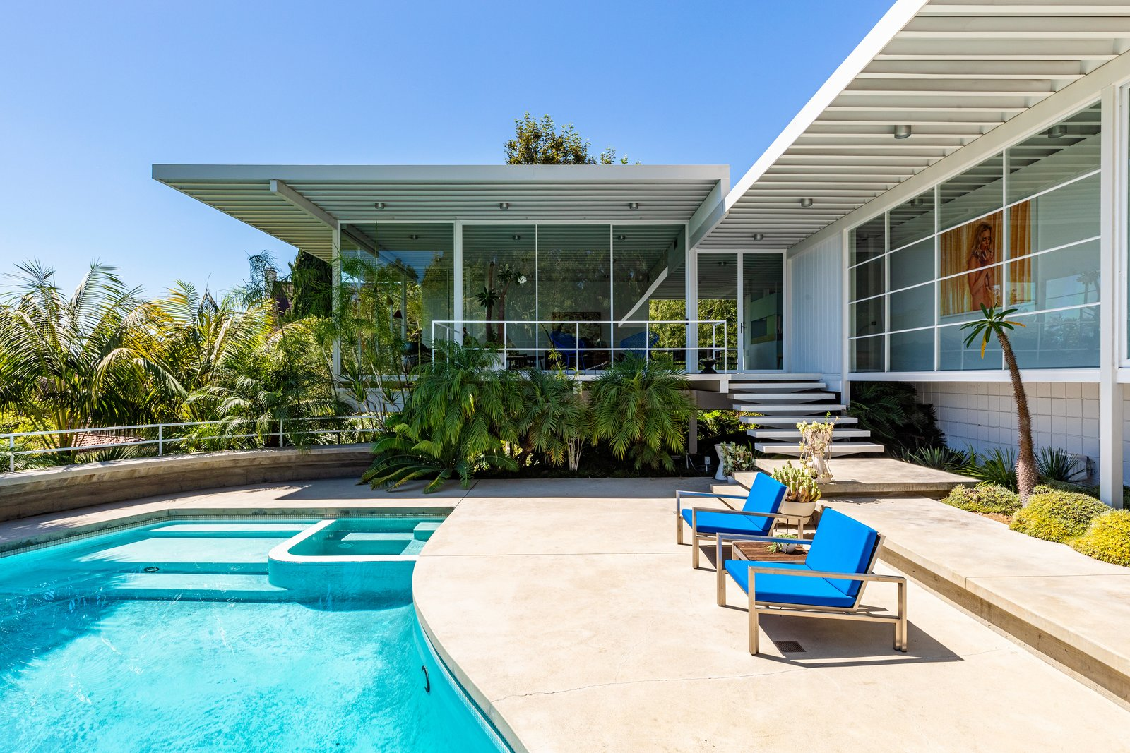 The pool and the pool deck were redone in the renovation. Updates introduced a semicircular bench with a railing at the perimeter, a hot tub, a wood-clad sauna, and a cold plunge pool.