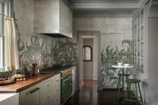 "The ferns encircle the kitchen and even camouflage the refrigerator. ""I worked with Tempest Tileworks here in Portland, who made each tile by hand and gave me guidance on how to paint with glaze, which I'd never done before,"" says Eng-Goetz. The green range is from Lacanche."