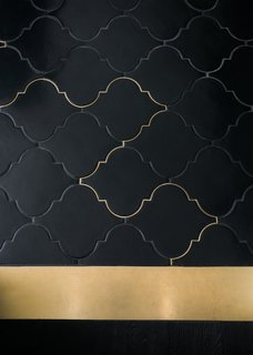 """Síol Studios added subtle brass details in the grout line where the kitchen flooring meets the island's brass backsplash. """"We wanted the color to spill into the grout line and weave its way from the threshold to the kitchen. The evening light catches this and illuminates the line for a moment,"""" explains Weigley."""