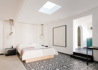 The renovated studio/pool house in the backyard features a bedroom, a kitchenette, and a bathroom. The bedside lighting is from Apparatus, and the Robusto cement floor tiles are from Clé. The tone-on-tone painting is by Trevor Paglen.