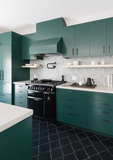 The cabinets were custom designed by Síol Studios and painted Deep Jungle—a bold shade of green from Pratt & Lambert. The backsplash features hand-painted terra cotta tiles by Walker Zanger. The oven range is from AGA Countertops. The floor is finished with hand-painted arabesque terra cotta tiles from Tabarka Studios.