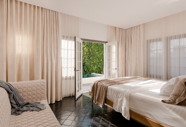 The master bedroom features the same hand-painted terra-cotta tile flooring as the kitchen.