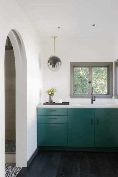 The kitchenette picks up the same green cabinetry as the kitchen in the main house. The pendant lighting is by Louis Weisdorf for Gubi.