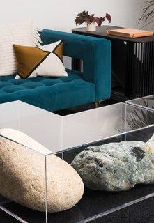 Nicole Wermer's work <i>Rock Bench #1</i> (boulders in a custom plexiglass case) serves as a coffee table.