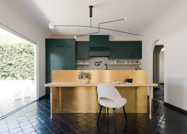 The insertion of a NanaWall opens the kitchen to the backyard and repositions the kitchen as the center of the home. The black chandelier above the kitchen island is Mobile #3 by Michael Anastassiades.