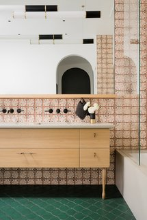 The master bathroom features arabesque terra-cotta tiles from Tabaraka Studios in a brilliant shade of green. The custom vanity has a concrete countertop with an integrated sink from Concreteworks and hardware from Marion Cage. The playful wall tiles are also from Tabarka Studios: Paris Metro #14 in charcoal and paprika. The turned leg is based on the turned column detail by the front door.
