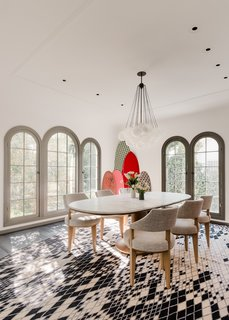 The dining room features a collection of surfboards from Barry McGee. The striking diamond-patterned rug is from Nanimarquina. An oval, marble-topped Mizar table from Giorgetti is paired with chairs from Dmitriy & Co and a Cloud chandelier from Apparatus Studio.