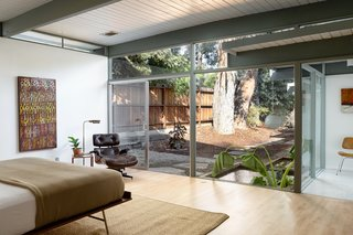 The master bedroom has glass sliders that open to a small terrace and the koi pond.