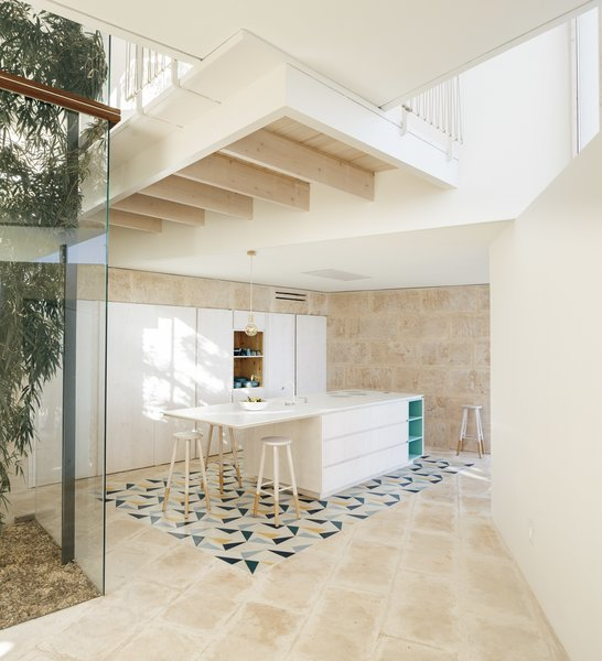 "Hydraulic cement tiles in the kitchen are presented in a ""carpet-like"" manner surrounding the kitchen island. The hexagonal tiles were designed by Reinpintado and manufactured by Mosaista. The custom millwork was designed specifically by Estudio Caballero Colón for this home."