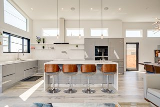 "This Bay Area family decided to splurge on top-of-the-line cabinetry by the Italian company, Cucine Lube because the kitchen would be the focal point of the open living space and where they predicted that they'd spend much of their time. The glossy panels are crafted from acrylic and glass dust to form a light and sturdy material that is ""as luminous as glass."" In addition, the panels are easy to maintain; resistant to water, heat, stains, and chemicals; and designed to be in contact with food—making it money well spent."