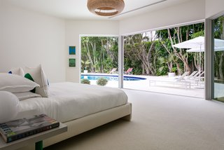 The master bedroom also features expansive glass sliders leading out to the pool area.