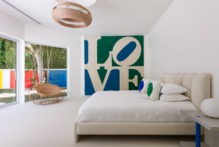 "The master bedroom features a blue and green ""Love"" wall hanging by Robert Indiana."