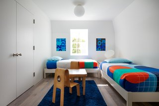 The children's bedroom fits two twin beds in an L-shape and a craft table.