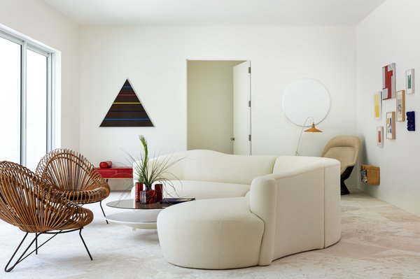 An undulating, ivory sofa gets prime placement right in the middle of Lisa Perry's living room.