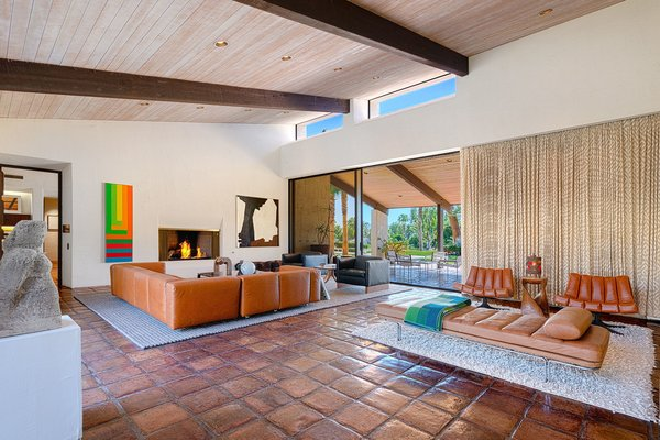 The soaring tongue-and-groove ceiling has clerestory windows at the top for added natural light. The wood beams are continued into the outdoor space. Glass sliding doors run the length of the space, seamlessly opening the entire home for indoor/outdoor entertaining.