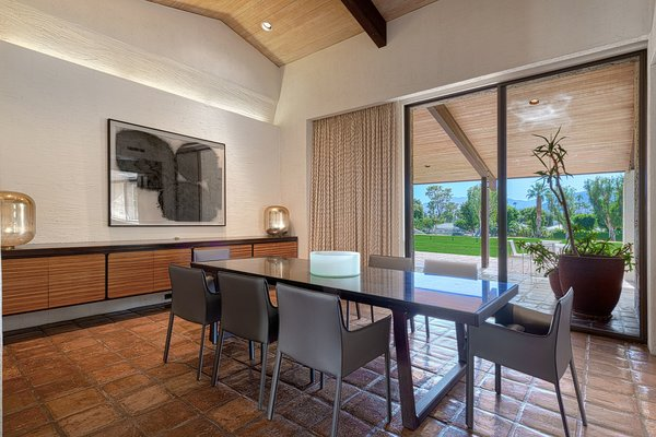 The dining room features built-in storage and glass sliders leading to an outdoor terrace.
