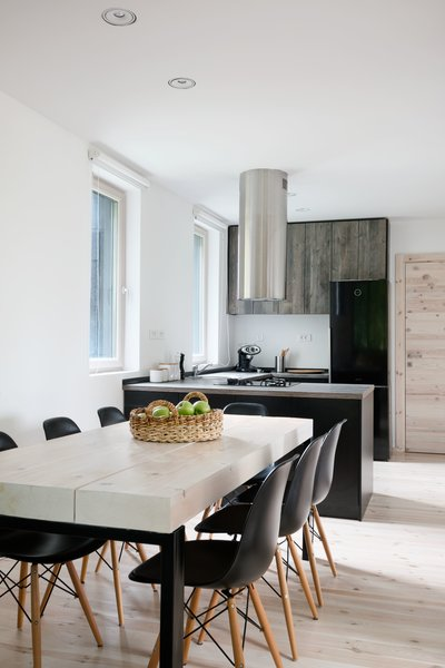 Sonja designed the dining room table using three solid fir beams that were treated by local craftsmen and set on top of a black steel base. The countertops are made of a composite laminate that has the texture and shade of weathered wood.