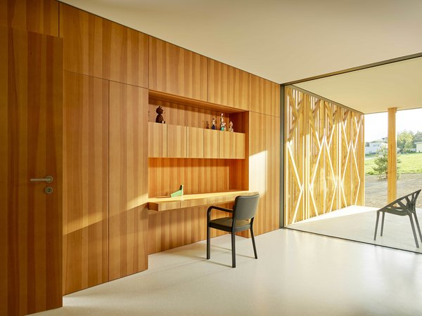 A wood-paneled, built-in desk nook is surrounded by cabinets.