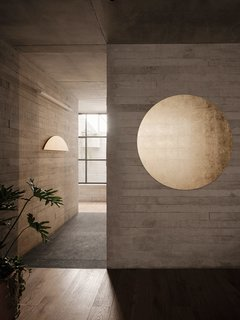 Two brassy pieces by Fervor—Sol Interior (the whole circle), and Sol Naciente (the half-circle)—serve to brighten the hallway.
