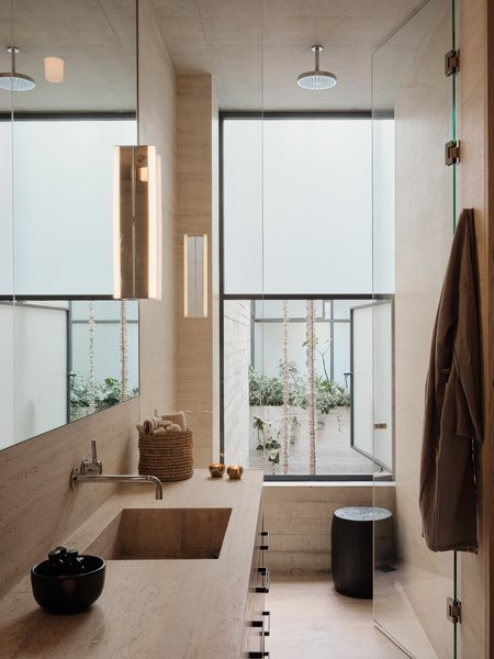The vanities and bathroom walls are made from locally sourced travertine slabs.