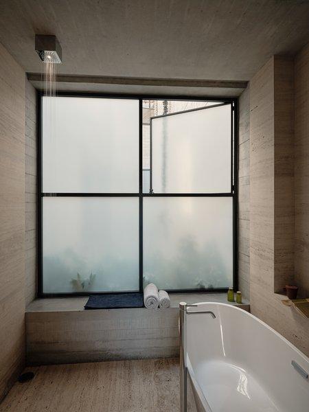 The master bathroom features an American Standard Coastal Serin freestanding tub and a  Viabizzuno Cubo Doccia shower head.