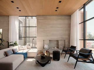 This living room features a custom sofa and leather, brass, and hardwood armchairs by Atra Form. A cluster of coffee tables includes the Paloma painted steel coffee table designed by Pedro Ramirez Vazquez, a custom brushed brass side table by Atra Form, and the Telugu Suar stained wood side table by NAMUH.