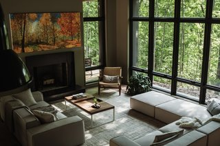 Full-height windows surround the living space and provide a strong indoor-outdoor connection to the sylvan surroundings. The sectional and coffee table are both from Rove Concepts