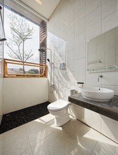 The upper-level bathroom has an indoor/outdoor feel. A pull-down shade provides privacy when needed.