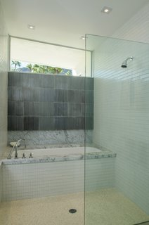 The second bedroom has a luxe spa-like feel with a marble-topped tub and an enclosed shower.