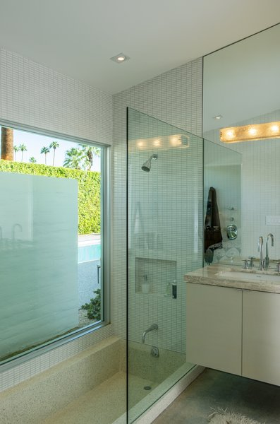 The master bathroom boasts a step-down terrazzo bathtub and a peek-a-boo view of the pool area.