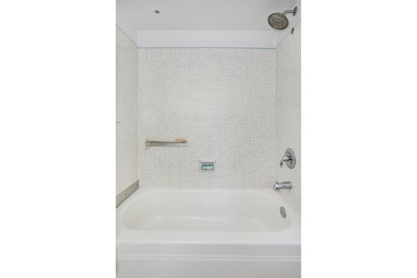 """There is no master bath, but this hall bathroom is accessible to all the bedrooms. """"The concept of a true, separate master bath wasn't invented until at least 1965,"""" says the seller. The vintage tiles are original to the home."""