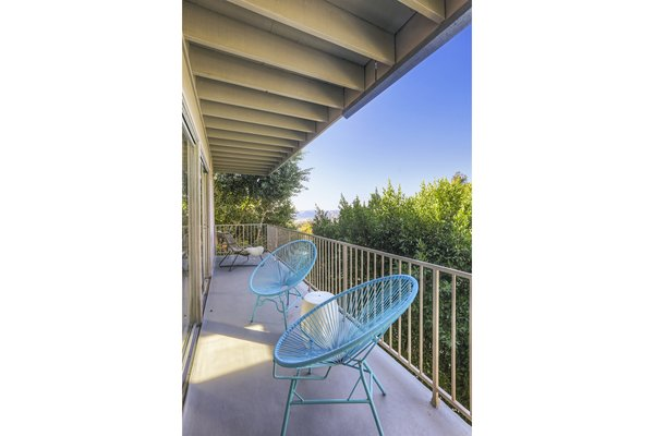 The balcony features treetop views and a connection to the outdoors.