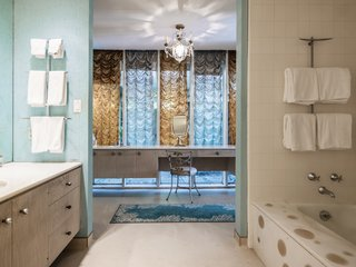 The master bath has a polka-dot soaking tub, and it opens to a dressing area.