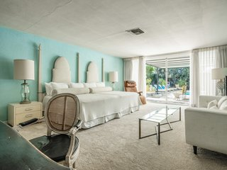 The master bedroom features oversized sliding glass doors that lead out to the pool area.