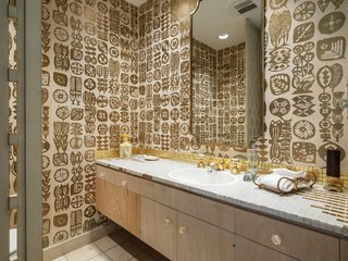 Tiny gold tiles wrap the countertop and play off graphic 1960s wallpaper in one of the home's five bathrooms.