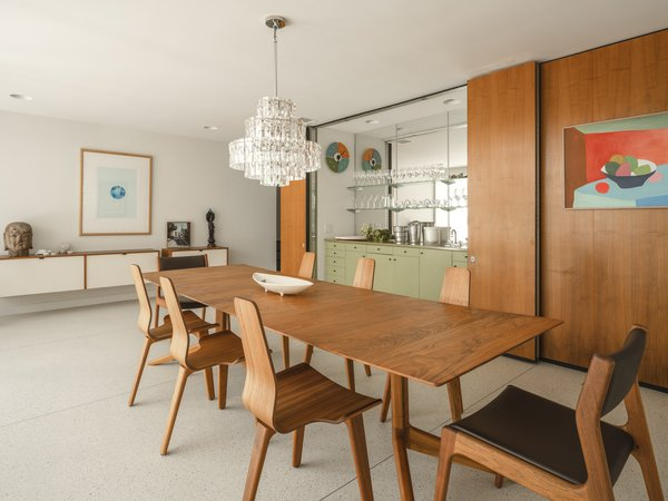 One of the highlights of the walnut-paneled dining room is the avocado green bar which is set behind a sliding door and is original to the home.