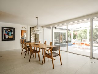 Oversized, full-height glass sliding doors provide easy access to the patio and a strong indoor-outdoor connection. The original terrazzo floors flow directly into the outdoors.