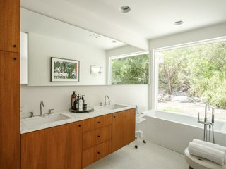 The updated master bath features a deep soaking tub and a serene view.
