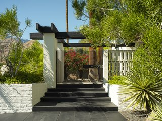 A post and beam entry plus a delicate brise soleil make up the entrance to 572 W Santa Elena Road.