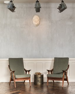 A pair of midcentury chairs in the lobby.  The wainscoting is repurposed from the building's original apartment doors.