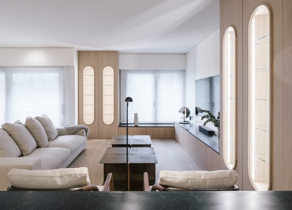 In the living room, oval-framed, oak wood display shelves and low-lying cabinetry match the large storage cabinet at the entrance. A Holden sofa by Verzelloni sits adjacent to Alison lounge chairs by Flexform. The table lamp is by Marset, and the reading lamp is by Vibia.