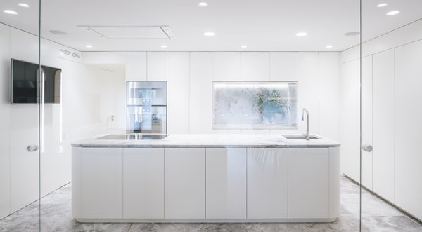 The all-white, minimalist kitchen is a transitional space between the public and private areas. A marble-topped island is oriented toward the dining room.