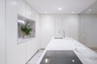 Ample, built-in storage lines the wall and the island. The appliances are from Gaggenau; the faucet from Cea Design.